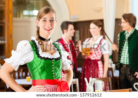 Young people in traditional Bavarian Tracht in restaurant or pub, one woman is standing in front, the group in the background - stock photo