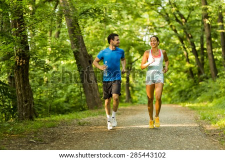 Young people jogging and exercising in nature - stock photo