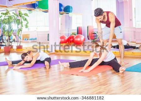 Young people lead a healthy lifestyle, exercise and engaged at fitness room. Instructor helping young girl doing stretching. Exercise strengthens a person physically and make them more happy! - stock photo