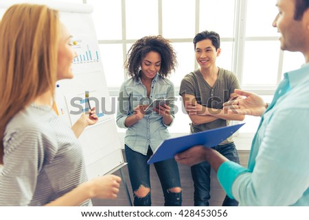 Young people of different nationalities are discussing business affairs, examining graphs and smiling. Afro American girl is using tablet - stock photo