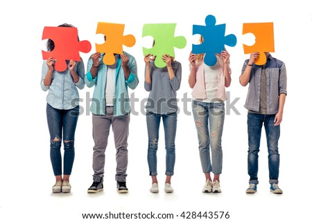 Young people of different nationalities are hiding faces behind colorful pieces of puzzle, isolated on white background - stock photo