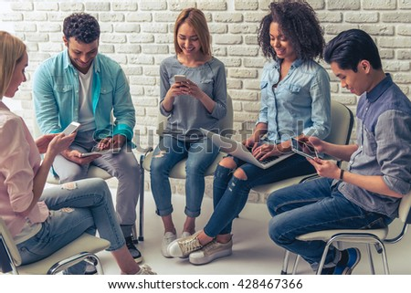 Young people of different nationalities are using gadgets and smiling while working in circle - stock photo