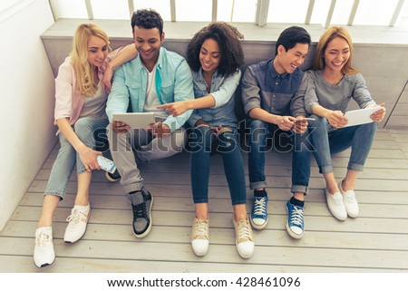 Young people of different nationalities are using gadgets, talking and smiling while sitting on the floor - stock photo