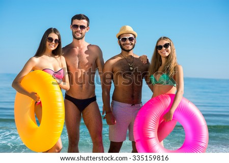 Young people on the beach. Funny friends resting in Monaco. Company on the sea. Guys and girls on the background of the sea. Summer holiday near the water. Woman in swimsuit. - stock photo