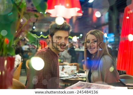 Young people on the night city restaurant (Pretty unique artistic image very hard to be taken in this conditions behind the night glass) - stock photo