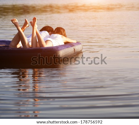 Young people on the swimming mattress on sunset - stock photo