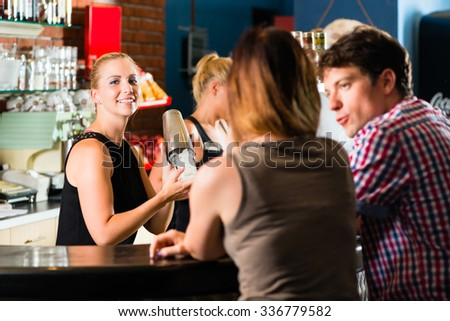 Young people or couple having a date in a club or bar, the bartender mixes a drink - stock photo