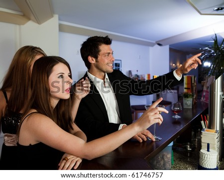 Young people ordering drinks at the bar. Focus on the girl - stock photo
