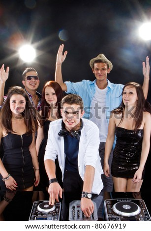 Young people partying to the music from the dj. Candid picture. - stock photo