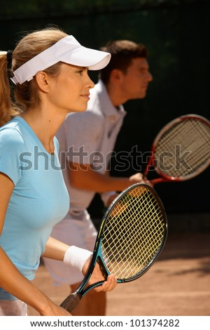 Young people playing tennis, mixed doubles, side view. - stock photo