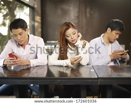 young people playing with smartphones and ignoring each other. - stock photo