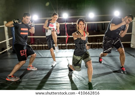 Young people practicing performer hit with hand in boxing ring - stock photo