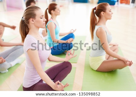 Young people practicing yoga in fitness club