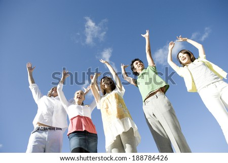 young people raising hands under blue sky - stock photo