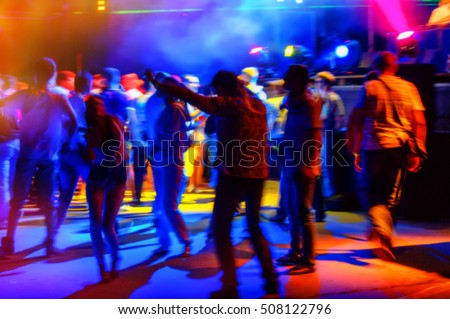 young people relax and dance in a disco night, blurred background
