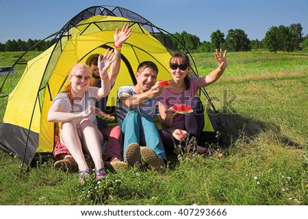 Young people relaxing on camping near the tent