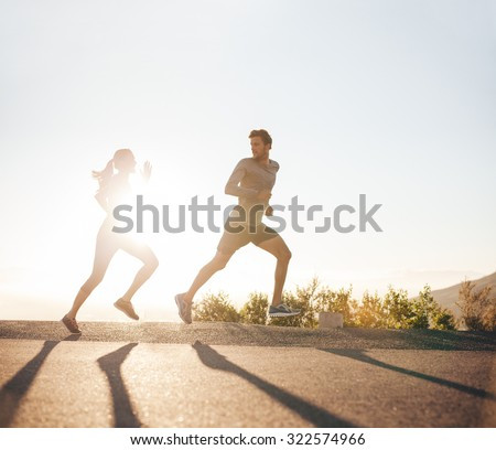 Young people running on country road with bright sunlight. Outdoor shot of young man and woman jogging in morning. - stock photo