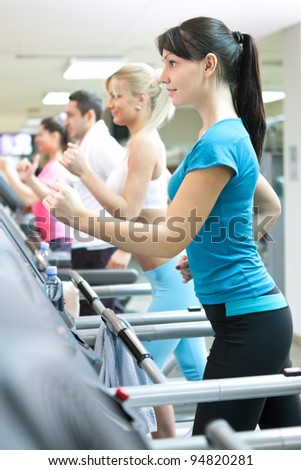 young  people running on treadmill in a modern fitness club - stock photo