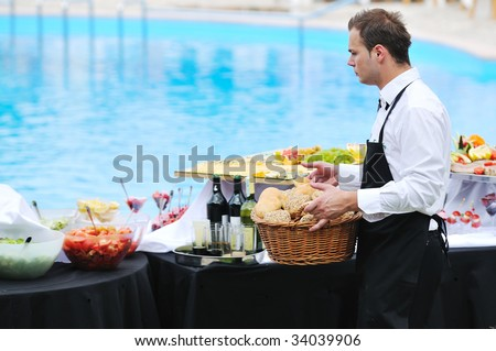young people serving food on buffet wedding seminar or conference outdoor party with fresh food and drink - stock photo