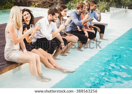 Young people sitting by swimming pool, drinking, having fun, enjoying holiday - stock photo