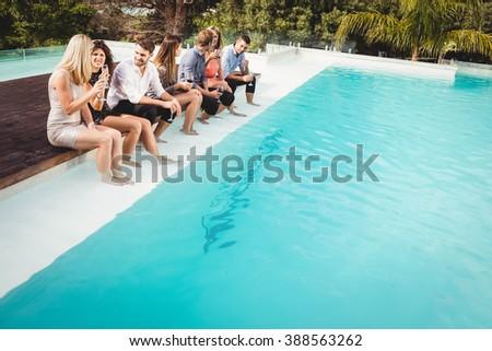 Young people sitting by swimming pool, drinking, having fun, enjoying holiday - stock photo