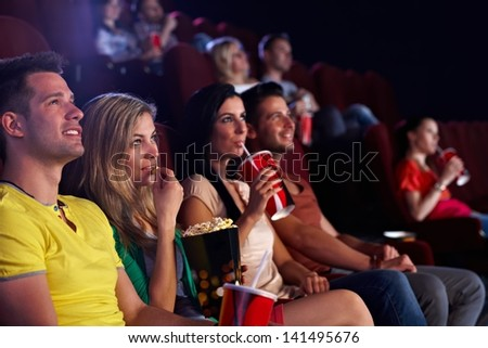 Young people sitting in multiplex movie theater, watching movie, eating popcorn. - stock photo