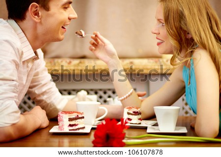 Young people sitting in the cafe and eating dessert, girl shares the cake with her boyfriend