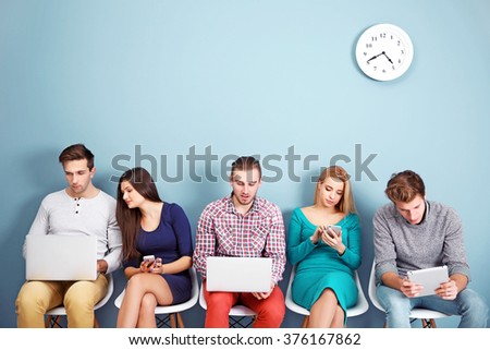 Young people sitting on a chairs and using devices in blue hall - stock photo