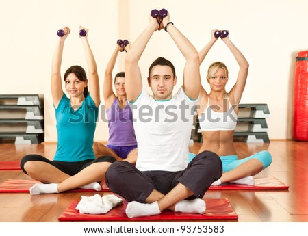 young people sitting on mats and doing exercises with dumbbell - stock photo
