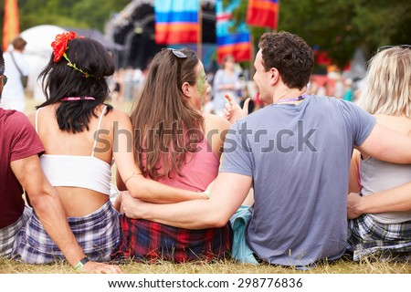 Young people sitting outdoors at a music festival, back view - stock photo