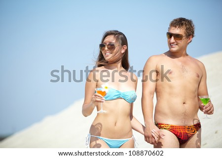 Young people smiling, holding hands and drinking cocktails on vacation - stock photo