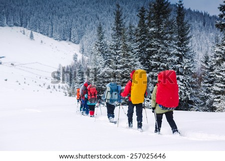 Young people snowshoeing - stock photo
