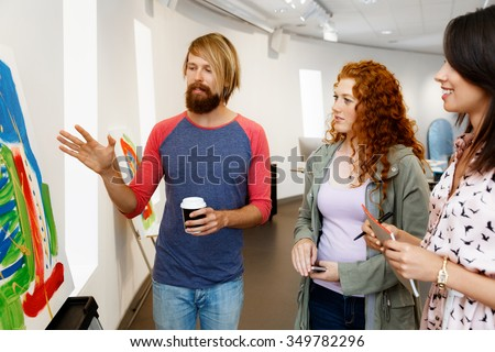Young people standing in a gallery and contemplating abstract artwork - stock photo