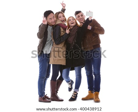 Young people taking selfie in their winter clothes isolated on white - stock photo