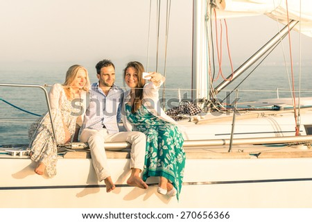 Young people taking selfie on exclusive luxury sailing boat - Concept of friendship and travel with best friends using modern smartphone as new trends and technology - Warm sunset color tones - stock photo