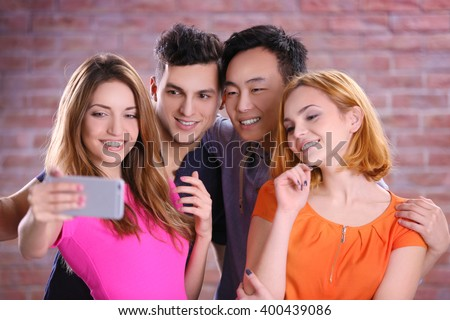 Young people taking selfie with mobile phone on brick wall background - stock photo