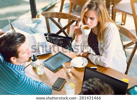 Young people talking over coffee at a table - stock photo
