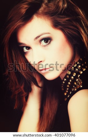 Young people teenage concept - pensive serious woman portrait, fashion teenager girl wearing blouse with gold metal stud on black