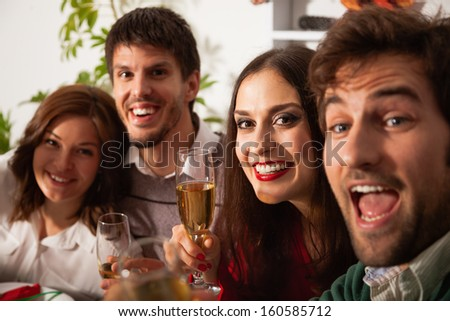 Young people toasting at Christmas eve. - stock photo