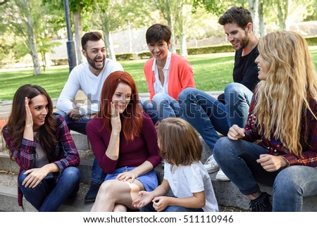 Young people together withe a little girl talking outdoors in urban background. Women and men sitting on stairs in the street wearing casual clothes.