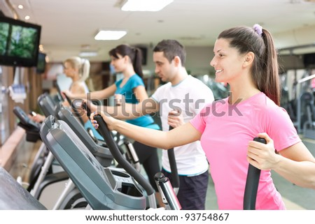 young people training on simulators in gym - stock photo