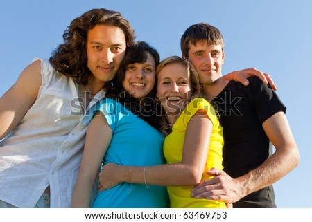Young people, two girls and two boys, hugged each other