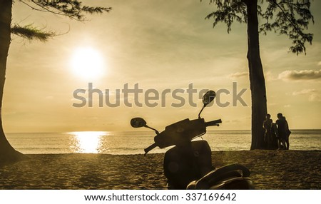 Young people walking along the beach. Sexy girls on the beach, standing next to Motorcycles. Friends stand under tree trunk against blue and yellow sky with sun  - stock photo