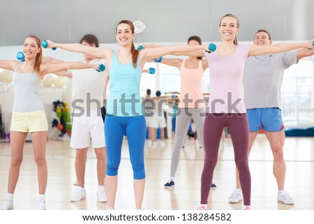 Young people with a dumbbell in fitness club - stock photo