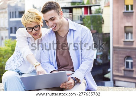 Young people with a laptop outdoors  - stock photo
