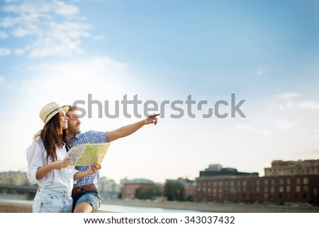 Young people with a map outdoors - stock photo