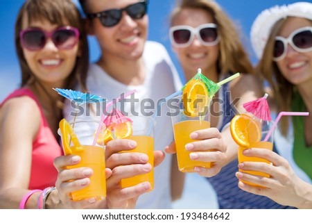 young people with cocktails in hand on the beach - stock photo