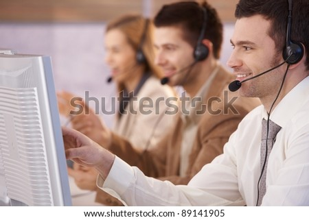 Young people working in call center, using headset and touch screen, smiling.? - stock photo