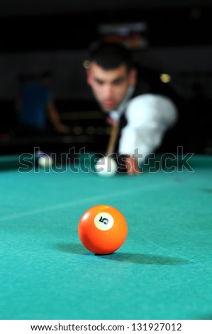 Young person playing snooker in a club
