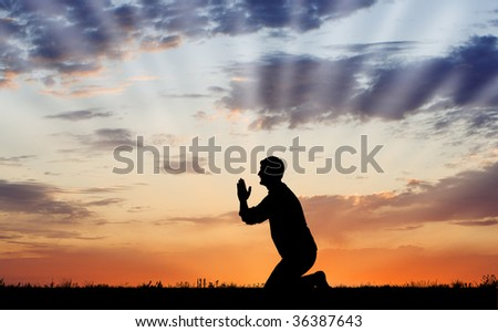 Young person praying in outdoor environment - stock photo